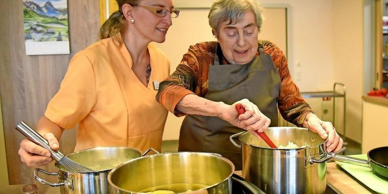 Pflegefachkraft kocht gemeinsam mit Bewohnerin im Haus alma