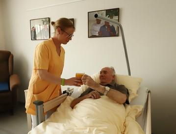 Pflegefachkraft reicht Trinken am Bett eines Bewohners