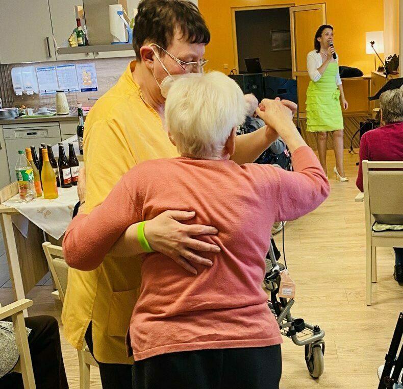 Bewohnerin tanzt mit Pflegerin zum Frühjahrsfest
