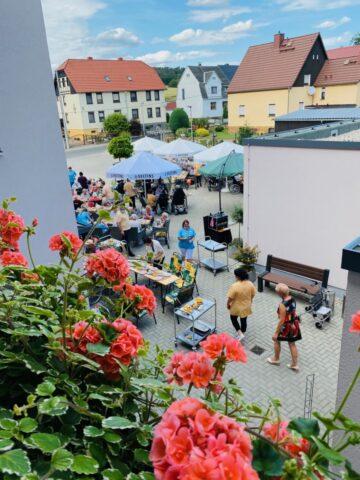 Blick vom blühenden Balkon auf das Sommerfest.